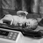 Newborn baby girl is being weight on a scale after birth.