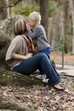 son-kissing-mom-holding-cheeks