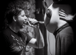Maternity photo of father singing into a microphone into expectant mother's belly.