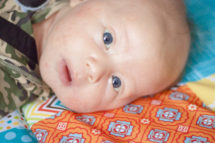 Baby boy laying on a play mat. his eyes are filled with wonder.